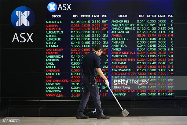 A cleaner sweeps the floor in front of an electronic board displaying stock information inside the Australian Securities Exchange operated by ASX Ltd...