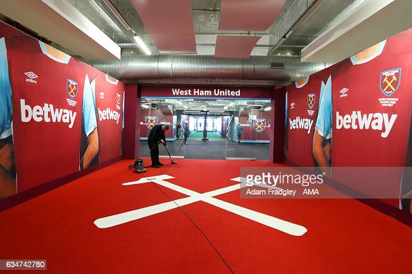 A cleaner vacuums the carpet in the tunnel before the Premier League match between West Ham United and West Bromwich Albion at London Stadium on...