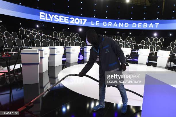 A cleaner vacuums the TV set before the debate organised by French private TV channels BFM TV and CNews between the eleven candidates for the French...