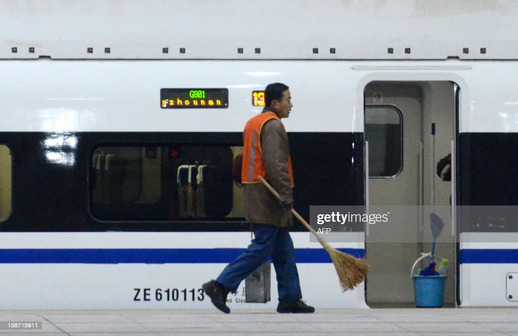 A cleaner walks past a high-speed train running from the Beijing to Guangzhou, south China's Guangdong province, at the Beijing west railway station in Beijing on December 26, 2012. China on December 26 started service on the world's longest high-speed rail route, the latest milestone in the country's rapid and sometimes troubled super fast rail network. AFP PHOTO / WANG ZHAO