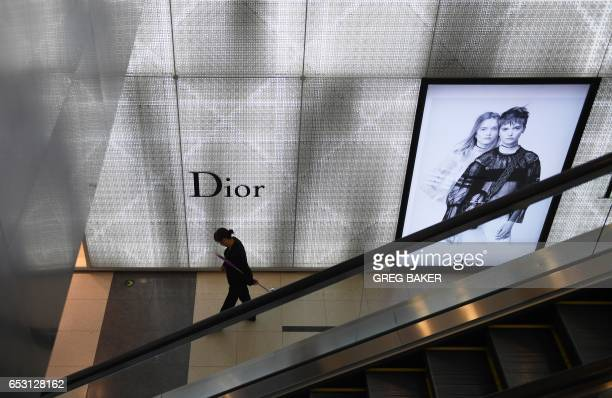 A cleaner walks past a luxury store at a shopping mall in Beijing on March 14 2017 China retail sales growth decelerated to 95 percent yearonyear in...