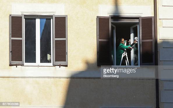 A cleaner wipes a window in a residential property after the Italian vote on constitutional reform referendum in Rome Italy on Monday Dec 5 2016...
