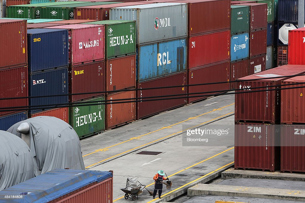 A cleaner works near stacked containers at the Port of Bangkok, Thailand, on Monday, Aug. 25, 2014. Thailand's trade figures are scheduled for release on Aug. 27. Photographer: Dario Pignatelli/Bloomberg via Getty Images