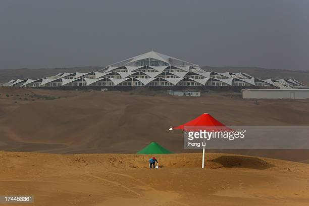 A cleaner works near the Desert Lotus Hotel in Xiangshawan Desert also called Sounding Sand Desert on July 18 2013 in Ordos of Inner Mongolia...