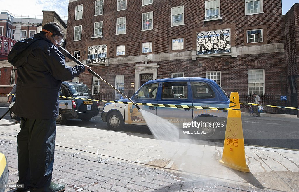 Cleaners spray the pavement outside the The Lindo Wing at St Mary's Hospital in Central London on July 24, 2013. Britain's Prince William and his wife Kate were spending their first day at home with their newborn son, a day after the world got its first glimpse of the little boy destined to become king. The Duke and Duchess of Cambridge spent the night at Kensington Palace after emerging from St Mary's Hospital in London with the unnamed baby boy in their arms, to huge cheers and a roar from the massed ranks of international media. AFP PHOTO / WILL OLIVER