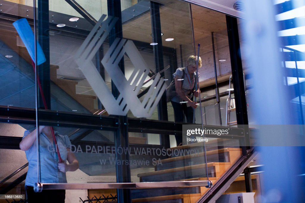 Cleaners work on a stairway displaying the WSE company logo at the Warsaw Stock Exchange in Warsaw, Poland, on Thursday, April 11, 2013. Poland's central bank kept interest rates unchanged at a record-low 3.25 percent yesterday. Photographer: Bartek Sadowski/Bloomerg