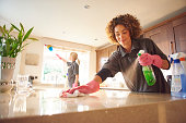 two professional cleaners in a domestic kitchen spraying cleaner onto a granite work surface .