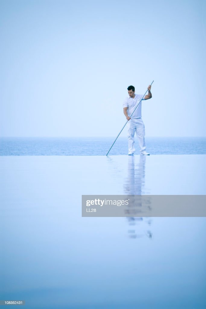 Cleaning a pool at dawn : Stock Photo