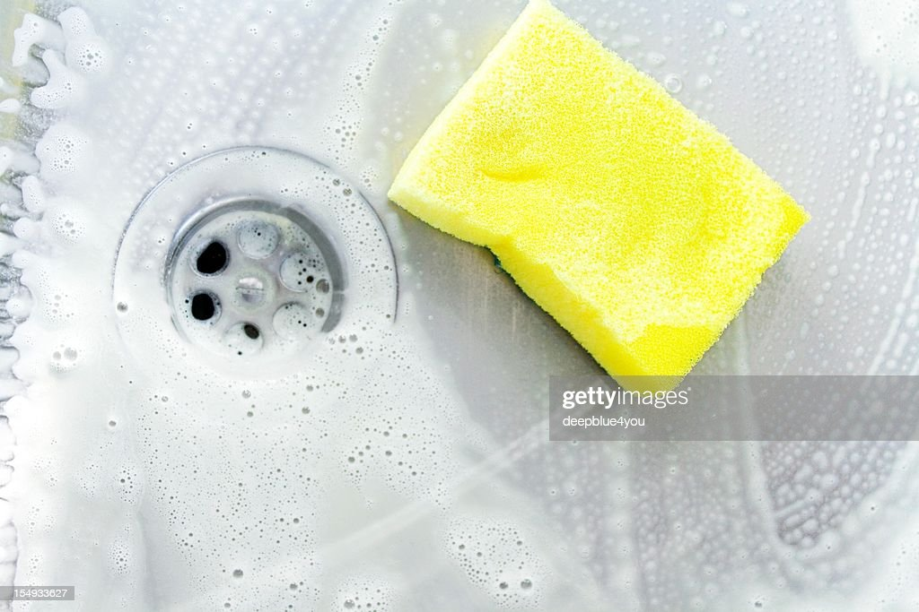 cleaning a sink with yellow sponge