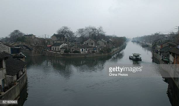 A cleaning boat sails at the 100 yearold Old Canal on February 7 2005 in Wuxi of Jiangsu Province China The pollution situation of the river has been...