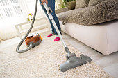 Cleaning carpet with vacuum cleaner in living room