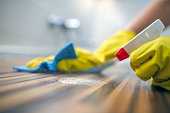 Photo of Woman or man cleaning kitchen cabinets with sponge and spray cleaner. Female or male hands Using Spray Cleaner On Wooden Surface. Maid wiping dust while cleaning her house wearing yellow prot