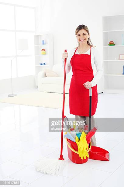 Cleaning lady standing in clean domestic room.