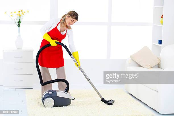 Cleaning lady vacuuming a bright living room.