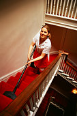 Cleaning lady vacuuming staircase