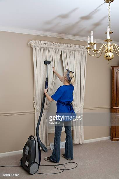 Cleaning- maid vacuuming curtain