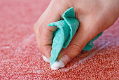 cleaning red carpet floor with rag and hand