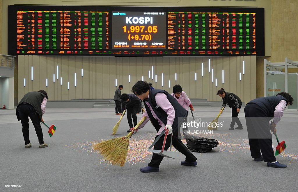 Cleaning staff sweep up confetti scattered by South Korean stock market staff to mark the closure of the 2012 trading year in Seoul on December 28, 2012. The benchmark KOSPI index closed the year at 1,997.05, up 9.4 percent from a year ago, despite a global economic slowdown.