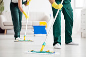 Cleaning team wiping the floor using mops in the flat