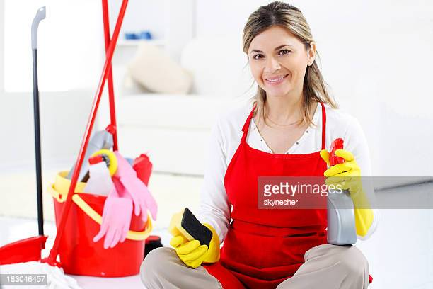 Cleaning woman holding  sponge and spray, looking at camera.