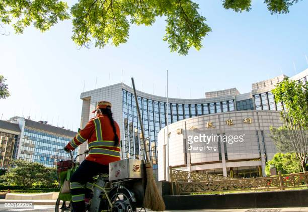 A cleaning worker rides her ebike past the PBoC To offer a longtime and sustainable financial support for the 'One belt One road' initiative China's...