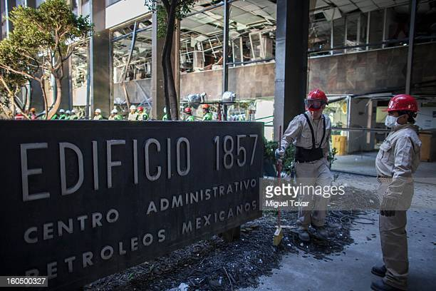 Cleaning workers sweep broken glass at the PEMEX administrative building on February 01 2013 in Mexico City Mexico Pemex is stepping up security at...
