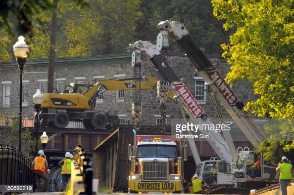 Cleanup continued as workers removed coal cars one by one on Wednesday August 22 following a derailment that killed two college students who were on...