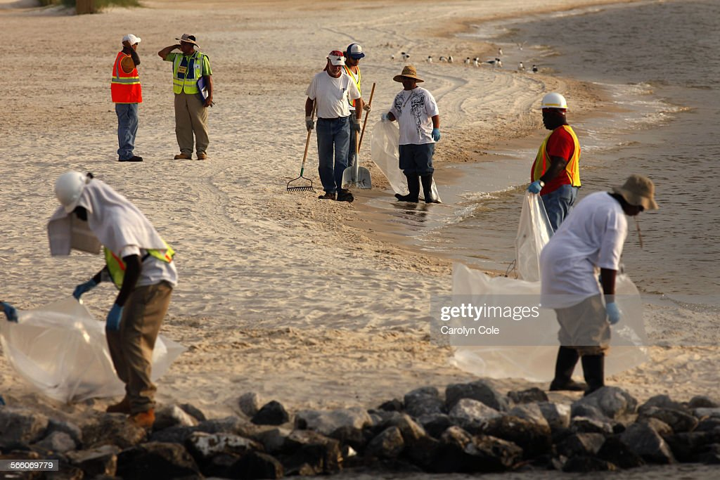 LAKESHORE MISSISSIPPI––JUNE 11 2010––A cleanup crew hired by BP contractors walks the beach in Lakeshore Mississippi near Waveland looking for trash...