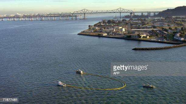 Cleanup crews aboard boats use a boom to contain oil north of Treasure Island 12 November 2007 in San Francisco Bay California A container ship...