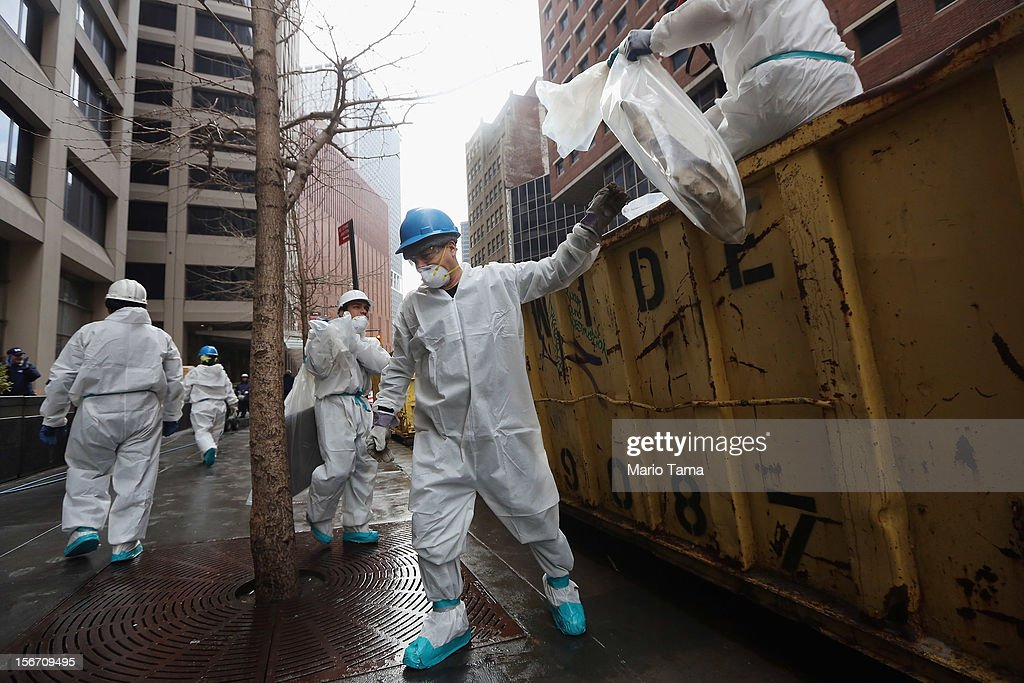 Cleanup workers discard material from a Financial District building that flooded following Superstorm Sandy in lower Manhattan on November 19, 2012 in New York City. Many of the office towers in the low lying Financial District which flooded remain closed due to damage to heating and electrical infrastructure. Many other buildings in the area are being powered by generators.