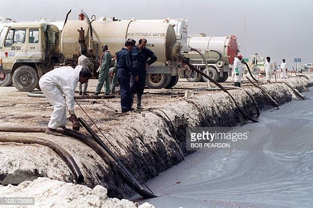 Cleanup workers pump oil from a manmade reservoir into waiting trucks 18 March 1991 Workers pump the oil from the waters of an adjoining bay to the...