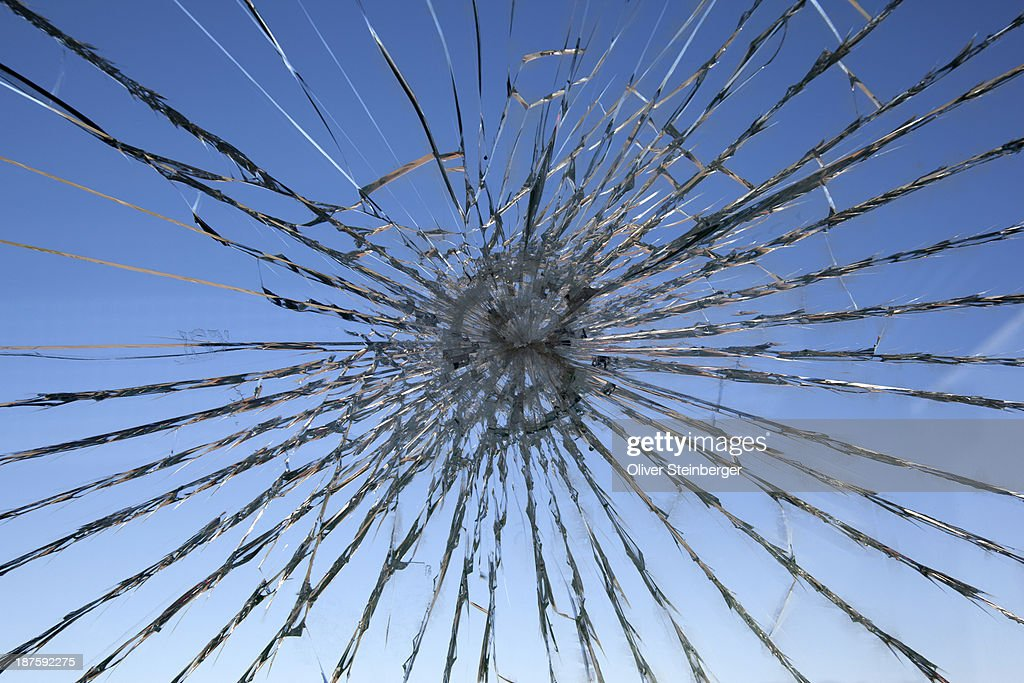 A clear blue sky seen through a shattered glass window