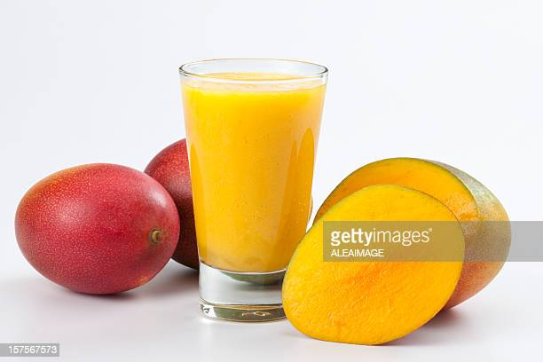 Clear full glass of mango juice with mangos laying beside