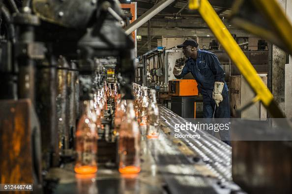Clear glass bottles cool after molding at the Nampak Ltd manufacturing plant in Roodekop South Africa on Friday Feb 26 2016 Already Africa's largest...