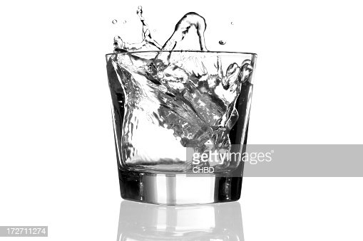 Clear glass with liquid splashing out because of ice