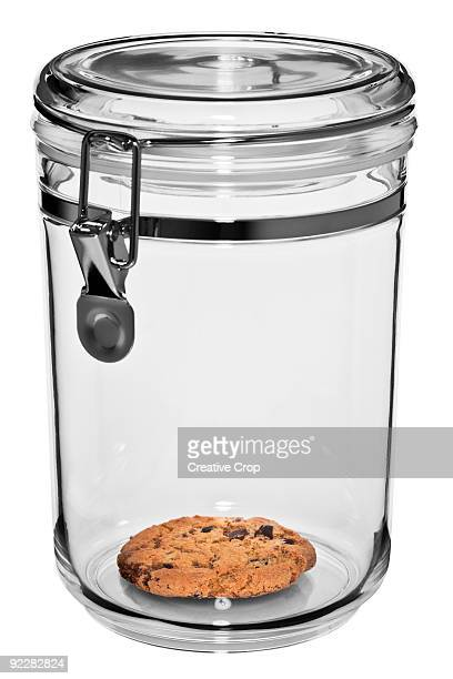 Clear plastic cookie jar with one cookie left