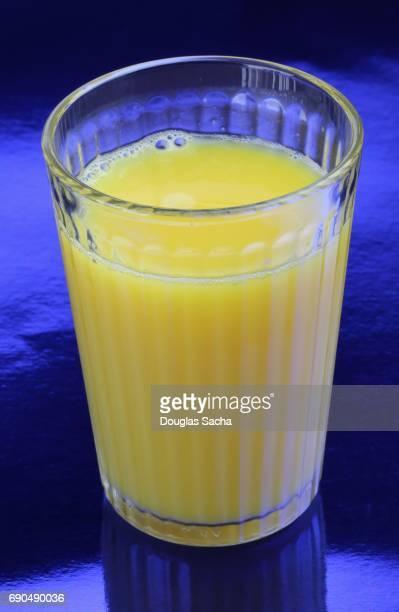 Clear serving glass of Orange Juice on a blue backround