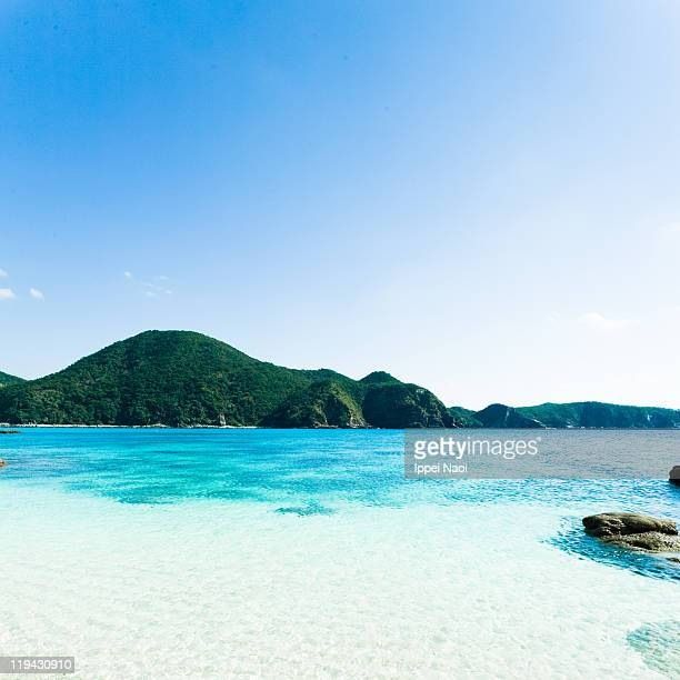 Clear tropical beach water with mountain, Okinawa