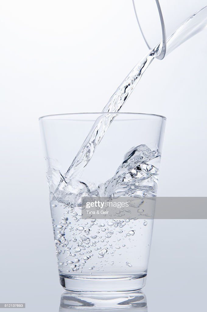 Clear water pouring from jug into drinking glass
