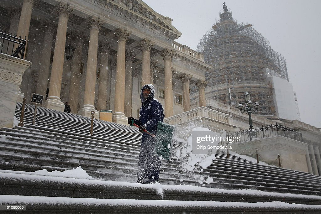 Clearing a path for the new Congress employees of the Architect of the Capitol shovel snow off the steps of the US House of Representatives as more...