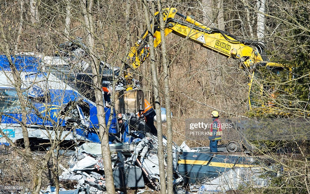 Clearing work is under way at the site of a train accident near Bad Aibling, southern Germany, on February 12, 2016. German investigators try to determine what caused the train crash that killed 10 people, while media reports said that human error was to blame. Two trains travelling at high speed crashed head-on February 9, 2016, in one of Germany's deadliest accidents in years, with one slicing the other apart, ripping a large gash in its side. / AFP / dpa / Peter Kneffel / Germany OUT