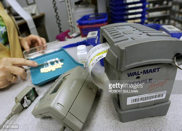 A WalMart pharmacist fills prescription drug orders 22 September 2006 at a store in Clearwater Florida WalMart has launched a program to cut the...