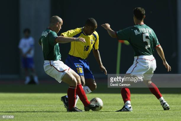 Cleber Chala of Ecuador takes the ball past Gerardo Torrado and Manuel Vidrio of Mexico during the FIFA World Cup Finals 2002 Group G match played at...