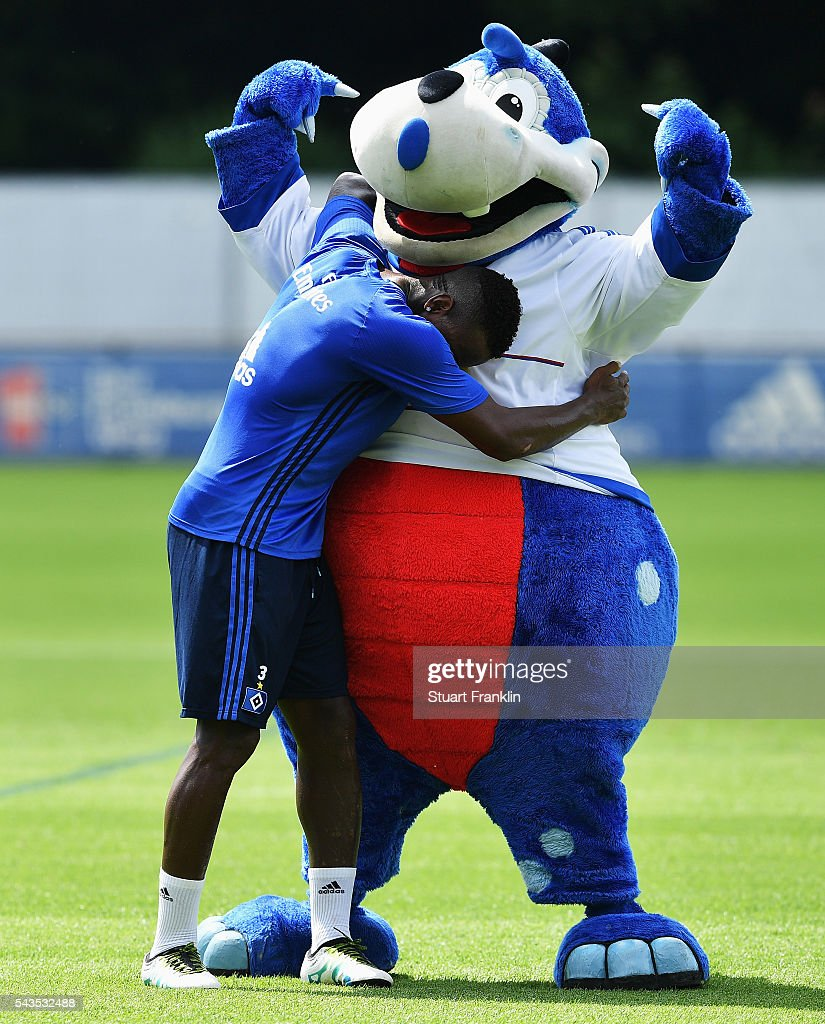 Cleber Reis hugs the club mascot Hermann during the first training session of Hamburger SV after the summer break on June 29, 2016 in Hamburg, Germany.