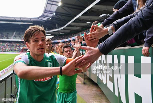 Clemens Fritz of Bremen celebrates with fans after the Bundesliga match between Werder Bremen and VfL Wolfsburg at Weserstadion on April 16 2016 in...