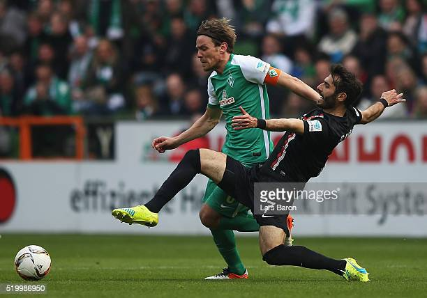 Clemens Fritz of Bremen is challenged by Halil Altintop of Augsburg during the Bundesliga match between Werder Bremen and FC Augsburg at Weserstadion...
