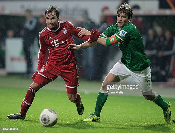 Clemens Fritz of Bremen tackles Mario Goetze of Bayern during the Bundesliga match between Werder Bremen and FC Bayern Muenchen at Weserstadion on...