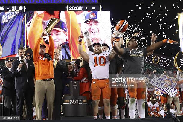 Clemson Tigers head coach Dabo Swinney holds up the National Championship Trophy on stage as Ben Boulware and Carlos Watkins celebrate with the the...