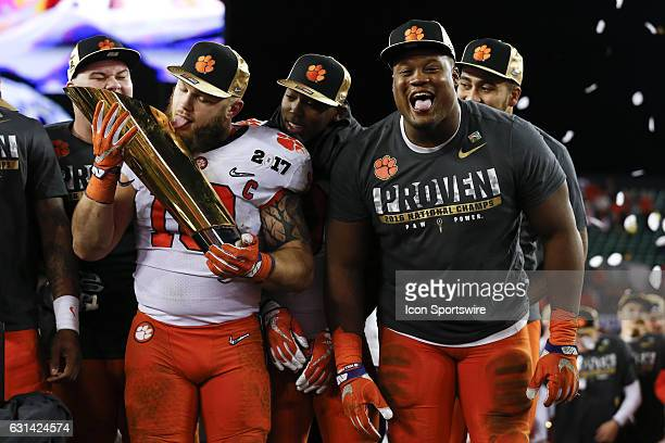 Clemson Tigers linebacker Ben Boulware licks the National Championship trophy as Clemson Tigers defensive tackle Carlos Watkins watches after the...