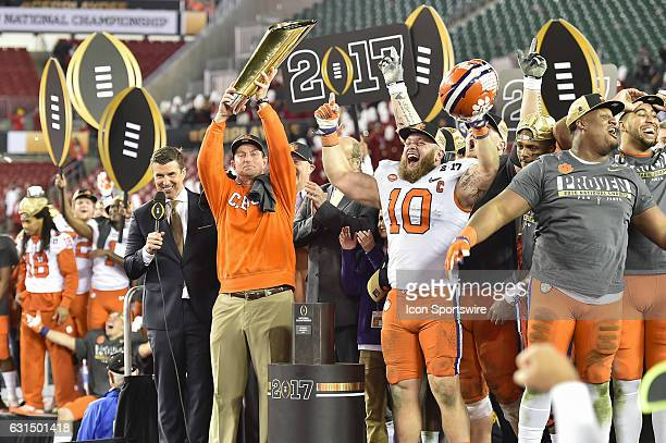 Clemson University head coach Dabo Swinney raises the National Championship trophy and Clemson University linebacker Ben Boulware celebrates during...
